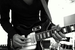 Photo of Psychedelic Indie Rock Music Artist Samuel Christen, half body photo playing guitar