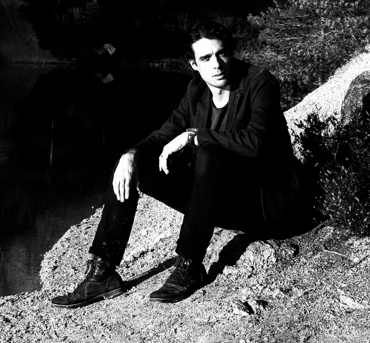 Photo of Psychedelic Indie Rock Music Artist Samuel Christen, full body photo sitting by the water