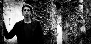 Photo of Psychedelic Indie Rock Music Artist Samuel Christen, half body photo with background ruins