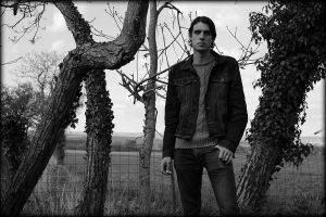 Photo of Psychedelic Indie Rock Music Artist Samuel Christen, full body photo in his garden