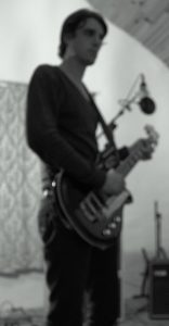 Photo of Psychedelic Indie Rock Music Artist Samuel Christen, full body photo in his home studio playing guitar
